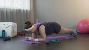 Meisje die grote inspanning leveren om zich in plankpositie te bevinden, die hard gewicht werken te verliezen stock footage