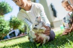 Meisje die haar bont klein huisdierenkonijn houden stock afbeelding