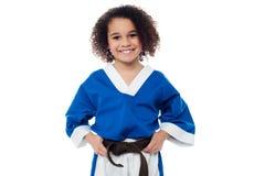 Meisje die haar bruine karateriem aanpassen Stock Foto's