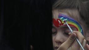 Meisje die haar die gezicht krijgen met regenboog door gezichts schilderende kunstenaar wordt geschilderd stock videobeelden