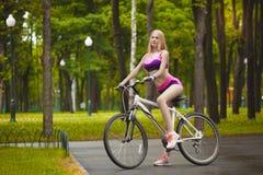 Meisje die haar fiets berijden op een Zonnige dag Stock Foto's
