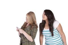 Meisje die haar friend& x27 proberen te bekijken; s tekstbericht Stock Fotografie