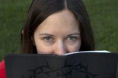 Meisje die haar gezicht achter een bijbel verbergen Royalty-vrije Stock Foto's