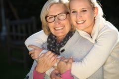 Meisje die haar grootmoeder omhelzen Stock Afbeelding
