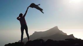 Meisje die haar hand golven bij de bovenkant van de berg stock footage