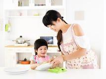 Meisje die haar helpen schone schotel in de keuken baren royalty-vrije stock afbeelding