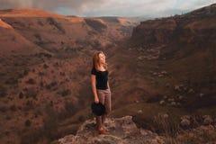 Meisje die haar hoed met achter haar golven onder ogen ziend de vallei met bergen aunset Canion nationaal park stock afbeelding