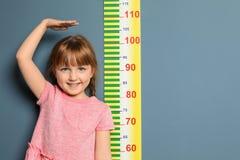 Meisje die haar hoogte meten stock foto