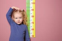 Meisje die haar hoogte op achtergrond meten royalty-vrije stock foto