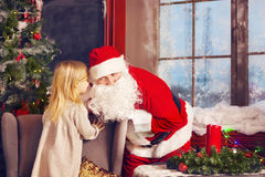 Meisje die haar Kerstmiswens in Santa Claus vertellen dichtbij C Royalty-vrije Stock Foto