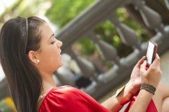 Meisje die haar mobiele telefoon met behulp van aan tekstbericht Royalty-vrije Stock Afbeelding