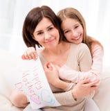 Meisje die haar moeder koesteren en greating kaart houden stock foto's