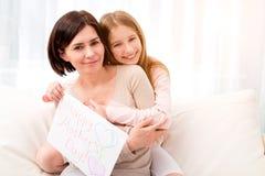 Meisje die haar moeder koesteren en greating kaart houden stock afbeeldingen
