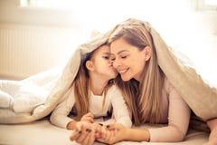 Meisje die haar moeder kussen onder deken stock foto