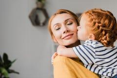 Meisje die haar moeder in wang kussen stock foto
