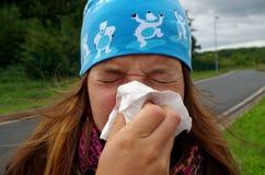 Meisje die haar neus blazen stock fotografie