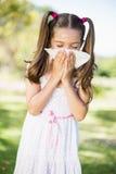 Meisje die haar neus met zakdoek blazen terwijl het niezen royalty-vrije stock afbeelding