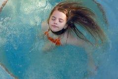 Meisje die haar ogen sluiten terwijl het spinnen rond in een pool Royalty-vrije Stock Foto
