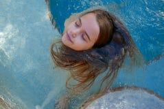 Meisje die haar ogen sluiten terwijl rond het spinnen van haar lang haar in een kuuroordpool Stock Foto's