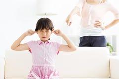 Meisje die haar oren behandelen terwijl haar boze moeder stock afbeelding