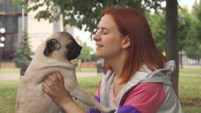 Meisje die haar pug kussen stock footage