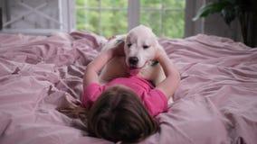 Meisje die haar puppy in slaapkamer strijken stock video