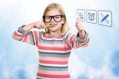 Meisje die haar tanden met schoolpictogrammen borstelen Stock Foto's