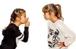 Meisje die haar zuster met haar vinger op vertellen te zwijgen Royalty-vrije Stock Afbeeldingen