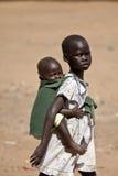 Meisje die haar zuster in Zuid-Soedan vervoeren Royalty-vrije Stock Afbeeldingen