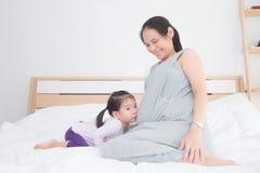Meisje die haar zwangere moederbuik op bed kussen royalty-vrije stock foto's