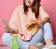 Meisje die Hamburger eten en de telefoon bekijken Het concept het de jeugdleven stock foto