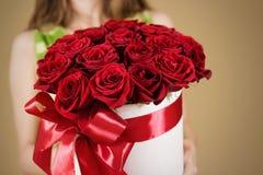Meisje die in hand rijk giftboeket van 21 rode rozen houden Composit Stock Afbeelding