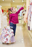 Meisje, die hangers met rok en blouse houden Stock Fotografie