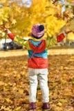 meisje die in heldere kleren met bladeren spelen stock afbeeldingen