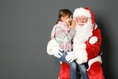 Meisje die in het authentieke oor van Santa Claus ` op grijze achtergrond fluisteren Royalty-vrije Stock Foto's