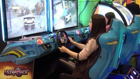 Meisje die het autospel van de simulator videoarcade spelen stock video