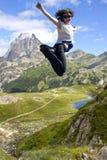 Meisje die in het midden van de bergen springen Royalty-vrije Stock Foto