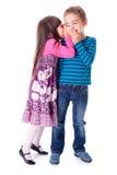 Meisje die in het oor van de jongen fluisteren stock fotografie