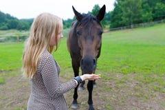 Meisje die het paard voeden royalty-vrije stock afbeelding