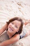 Meisje die in het zand glimlachen Royalty-vrije Stock Foto's