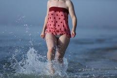 Meisje die in het zeewater lopen Royalty-vrije Stock Afbeelding