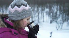 Meisje die hete drank in openlucht in de winter drinken stock videobeelden