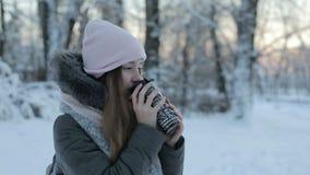 Meisje die hete thee of koffie van feestelijke kop met sneeuwpark drinken stock video