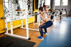 Meisje die hurkzit met een barbell doen bij de gymnastiek concept een gezonde levensstijl stock fotografie