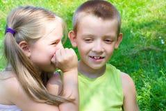 Meisje die iets fluisteren aan haar broer stock fotografie