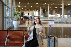 Meisje die Internet gebruiken door tablet in luchthavenzaal valise dichtbij en duimen het tonen Royalty-vrije Stock Fotografie