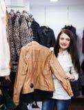 Meisje die jasje kiezen bij kledingsopslag Stock Foto