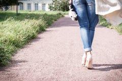 Meisje die in jeans langs de weg van de camera, achtermening, hoge hielschoenen lopen stock foto