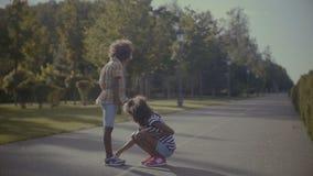 Meisje die jongere zuster helpen om schoenen te binden stock footage