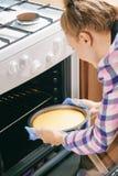 Meisje die kaastaart nemen uit oven in keuken stock foto's